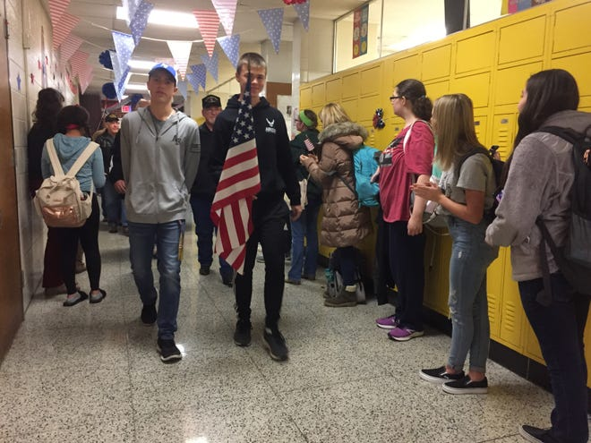 A pair of Lexington high school students carry Old Glory ahead of a veterans' walk Monday.
