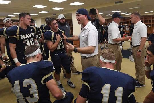 Head coach Jason Dewald, a Mansfield Senior HIgh grad, speaks to members of the Navy sprint football team, whose players can weigh no more than 178 pounds.