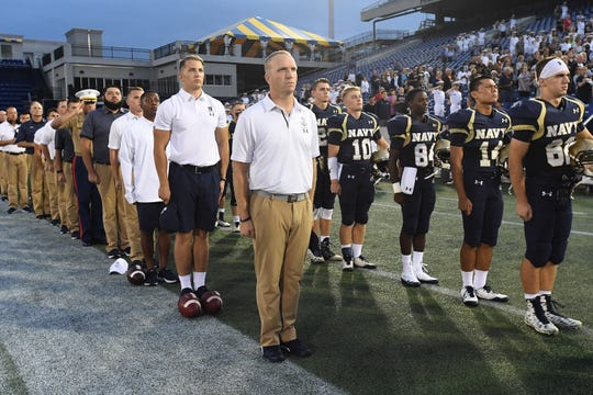 Head coach Jason Dewald, front left, stands at attention with members of the U.S. Navy's CSFL team before a game.