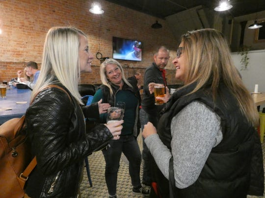 Brooke Wall, left; Jill Hecker, center; and Heather Harper, right, enjoy beers at Marion Brewing Company on Friday.