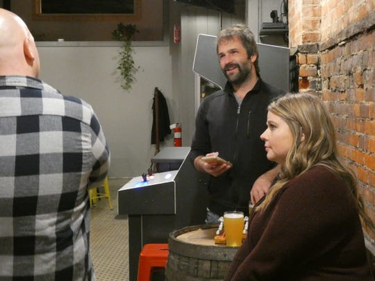 JT Burke, center, and Amanda Johnson, right, enjoy a beer at the Marion Brewing Company.