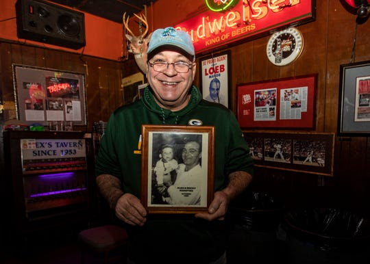 Rocky Kasaftes holds a photograph of himself and his farther inside of Alex's Tavern on Jackson Ave Thursday Nov. 7, 2019.