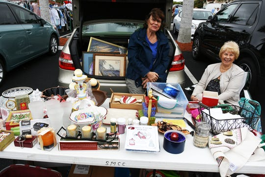 Traudel Scampa, left, and Ginger Loughrey with their treasures. Treasures in the Trunk, a group rummage sale, was held Saturday by the Columbiettes of San Marco Catholic Church.