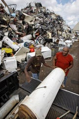 Willie Rogers, right, and his brother Roosevelt Rogers, both from Milwaukee, help a friend unload his water heater, which was damaged by flooding, at United Milwaukee Scrap, 3232 W. Fond du Lac Ave., on July 28, 2010.