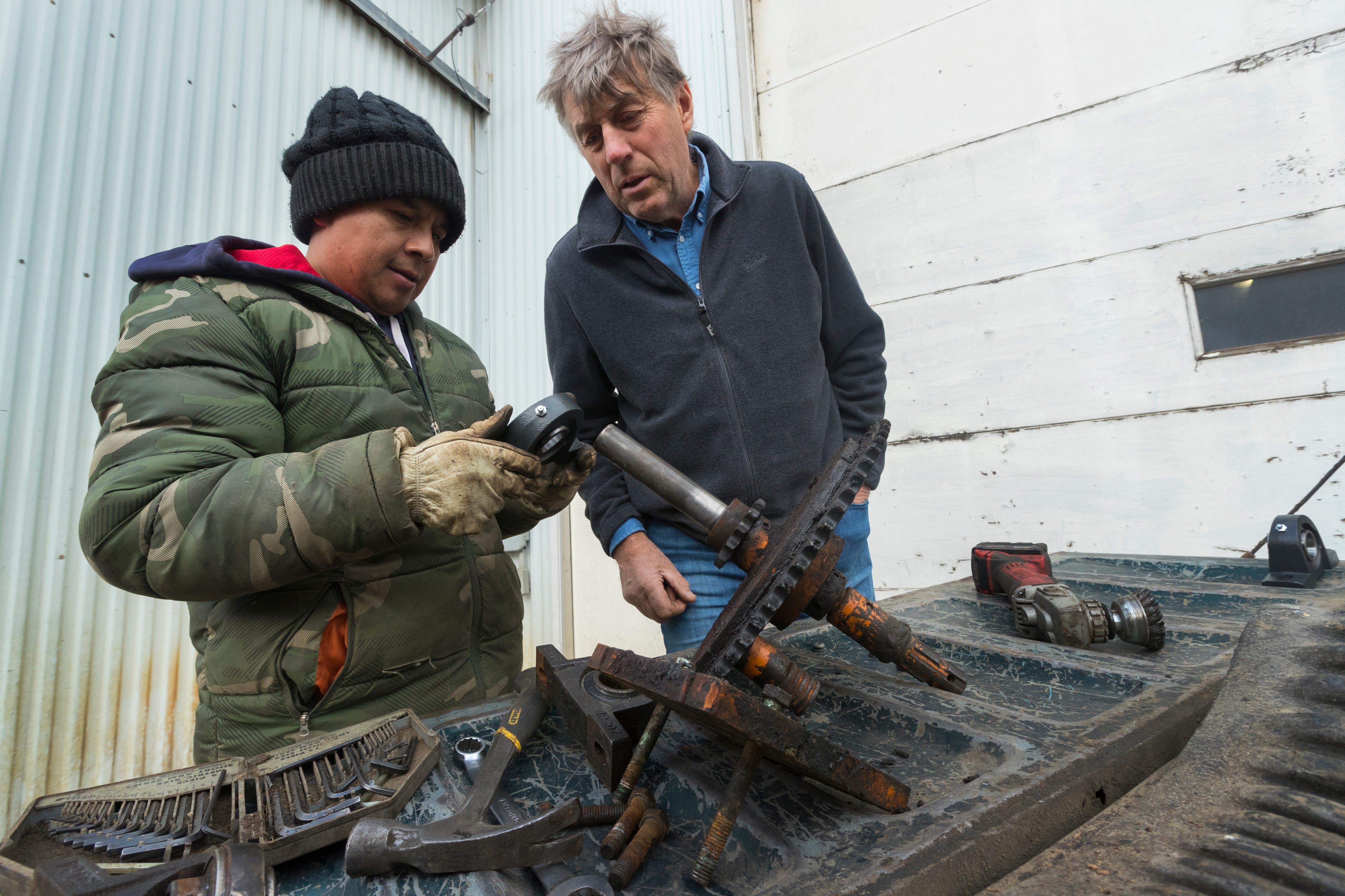 Roberto Tecpile, left, a Mexican immigrant, replaces the bearings while repairing an irrigator with the help of dairy farm owner John Rosenow at Rosenholm Dairy in Cochrane.
