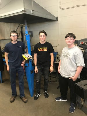 Three Pewaukee High School boys are helping out with creating letters for a damaged small vehicle bridge on Clark Street in the village of Pewaukee. From left to right: Luke Hesprich, Peyton Guyot and Richard Loescher stand