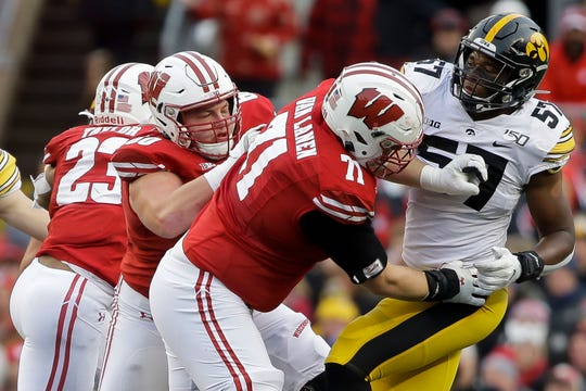 Wisconsin linemen Logan Brussand Cole Van Lanen (71) block Iowa defensive end Chauncey Golston.