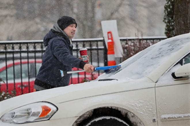 A motorist parked in the 1000 block of North Old World 3rd Street balanced his coffee as he brushed snow off his windshield.