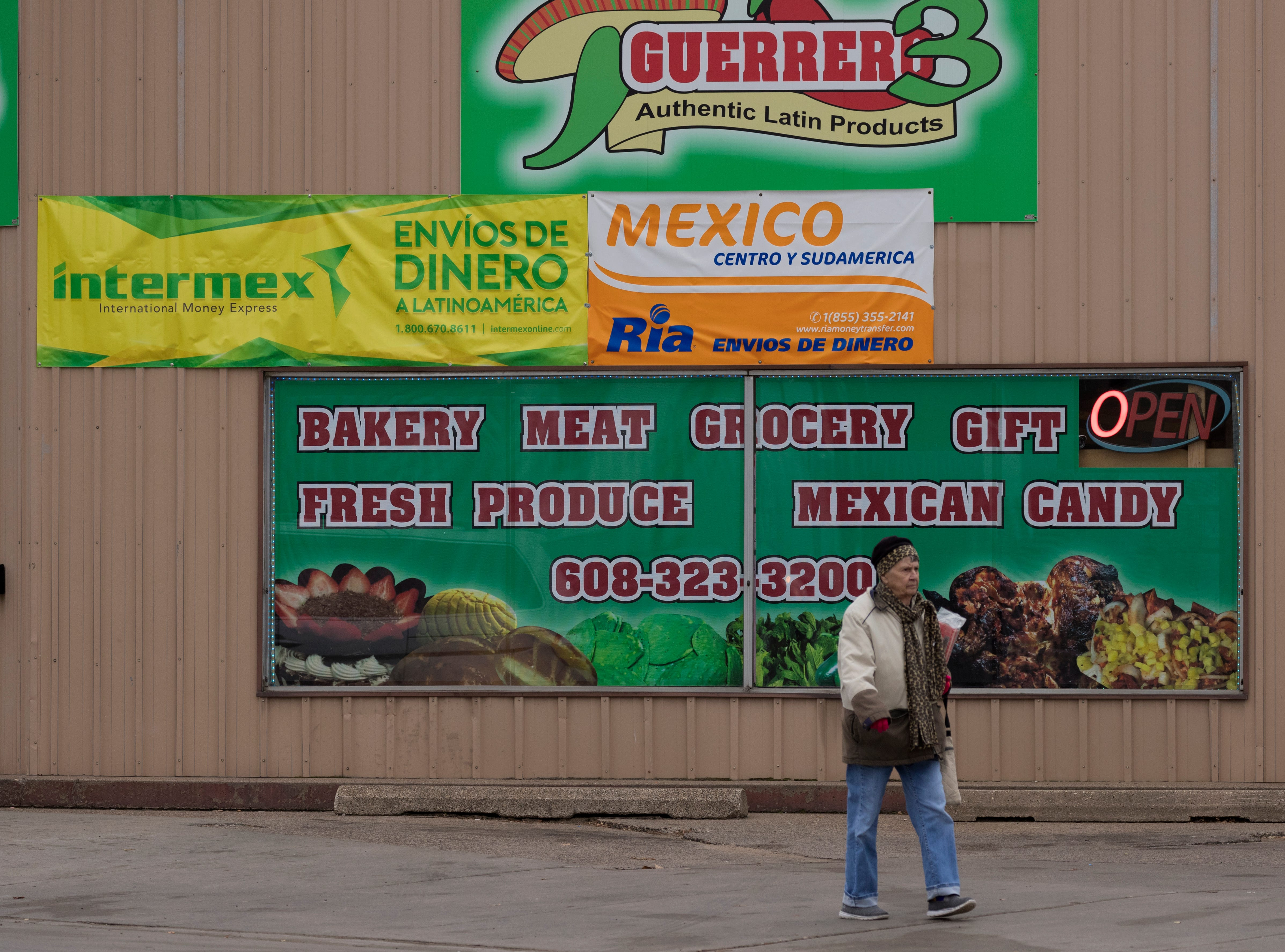 A pedestrian walks past one of a number of businesses that cater to Mexican immigrants in Arcadia in western Wisconsin.