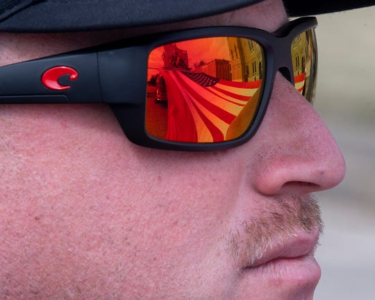 The Amervcian flag is reflected in the sunglasses of Prattville fire medic Kenny Barber at the Veterans Day Observance in Prattville, Ala., on Monday November 11, 2019.