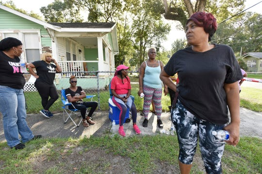 A group of women on Ivy Street gathered in the morning Thursday, Nov. 7, 2019 and were still waiting at 3 p.m. for news about 5-year-old Taylor Rose Williams, who went missing in the area around midnight Wednesday in Jacksonville, Fla. (Will Dickey/The Florida Times-Union via AP)