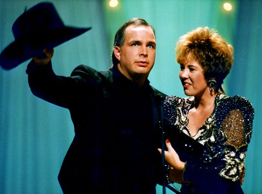 """Sandy Brooks joins husband Garth Brooks onstage as he accepts the Entertainer of the Year award during the CMA Awards show at the Grand Ole Opry House on Sept. 30, 1992. Brooks also won Album of the Year for """"Ropin' the Wind."""""""