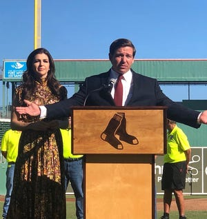 Florida Gov. Ron DeSantis, beside first lady Casey DeSantis, addresses a Veterans Day crowd Monday, Nov. 11, 2019, at JetBlue Park in Fort Myers.
