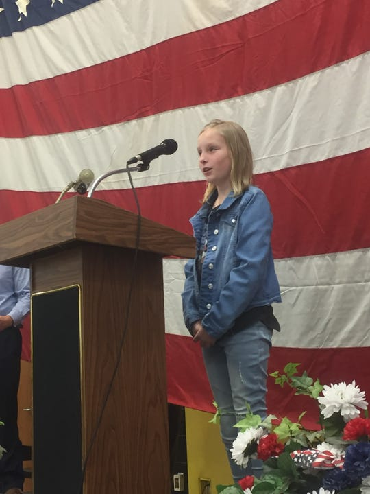 "Taylor Hamper reads, ""Soldiers Are Heroes,"" during the Nov. 11 Etna Elementary School Veterans Day program."