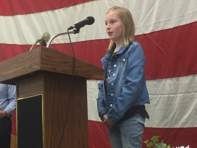 """Taylor Hamper reads, """"Soldiers Are Heroes,"""" during the Nov. 11 Etna Elementary School Veterans Day program."""