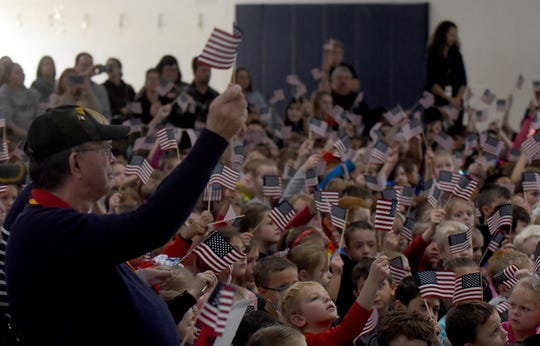 Army veteran William Richards waves a flag along with Legend Elementary students during the school's Veterans Day program on Monday, November 11. Richards also works for Newark City Schools.