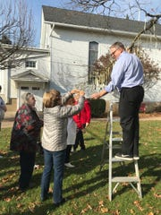 First Presbyterian Church of Ramsey members help Rev. Steve Huston hang 22 dog tags from their 'Witting Tree' to remind residents of elevated suicide rates among military service members.