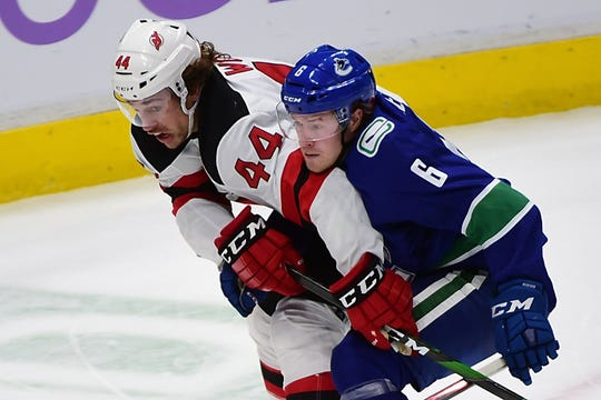 New Jersey Devils forward Miles Wood (44) battles for the puck against Vancouver Canucks forward Brock Boeser (6) during the second period at Rogers Arena.