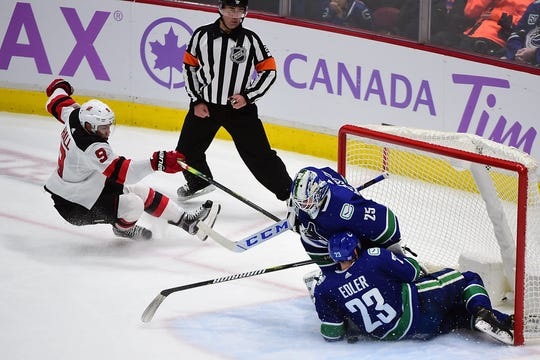 Vancouver Canucks defenseman Alexander Edler (23) and goaltender Jacob Markstrom (25) defend the goal against New Jersey Devils forward Taylor Hall (9) during the third period at Rogers Arena.