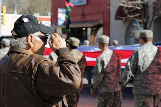 A man salutes a flag carried by passing JROTC students from Aztec High School in Aztec on Nov. 11, 2019, Veterans Day.