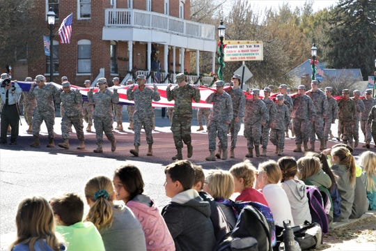 Local elementary school students watch a passing procession of JROTC students from Aztec High School in Aztec on Nov. 11, 2019, Veteran's Day, during the annual Veterans Day Parade in Aztec.