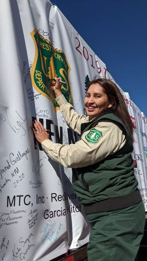 Erica Enjady adds her name to the protective cover of the Capitol Christmas tree.