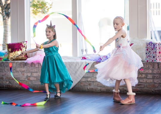 Ensley Webster, 7, right, spins around Monday with friends during her cupcake shop-themed dance party in downtown Pensacola. The event was hosted by the Rally Foundation and Covenant Care's My Wish.