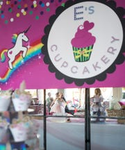 Ensley Webster, 7, center, spins around while twirling a ribbon Monday during her cupcake shop-themed dance party in downtown Pensacola.