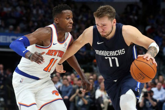 New York Knicks guard Frank Ntilikina (11) covers Dallas Mavericks guard Luka Doncic (77) as he drives the ball in the second half in an NBA basketball game Friday, Nov. 8, 2019, in Dallas. (AP Photo/Richard W. Rodriguez)
