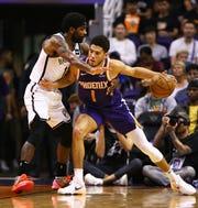 Brooklyn Nets guard Kyrie Irving (11) pressures Phoenix Suns guard Devin Booker (1) in the first half on Nov. 10, 2019 in Phoenix, Ariz.