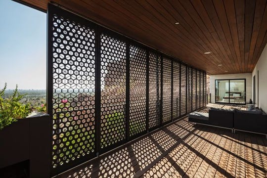 Custom screens on the home's second-story patio balance filtered light with incredible views of the city.