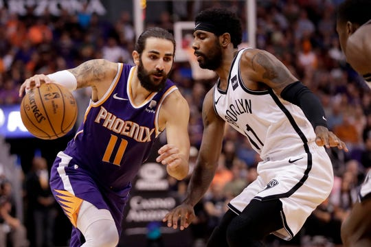 Phoenix Suns guard Ricky Rubio, left, drives past Brooklyn Nets guard Kyrie Irving, right, during the first half of an NBA basketball game, Sunday, Nov. 10, 2019, in Phoenix. (AP Photo/Matt York)