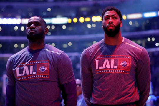 LeBron James and Anthony Davis listen to the national anthem before a game against he Raptors on Sunday at Staples Center.