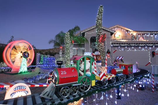 """Every year, Frank and Dianne Polimene debut their Ahwatukee """"train house"""" on Thanksgiving Day and operate through the New Year. This year, their self-made Christmas train, Ferris wheel, and artificial snow show will be featured on HGTV's """"Outrageous Holiday Houses"""" special on Nov. 28 at 9 p.m."""