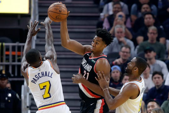 Portland Trail Blazers center Hassan Whiteside (21) passes the ball while defended by Golden State Warriors forward Eric Paschall (7) and guard Alec Burks during the first half of an NBA basketball game in San Francisco, Monday, Nov. 4, 2019. (AP Photo/Jeff Chiu)