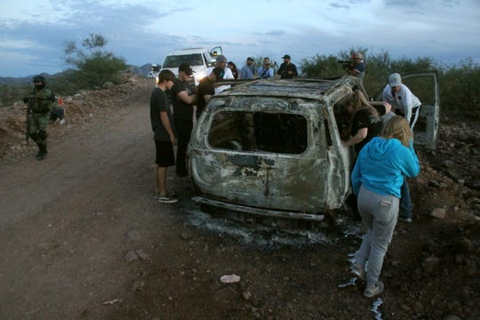Miembros de la familia LeBarón observan el vehículo calcinado donde fueron ultimados sus familiares cuando circulaban por las comunidades de Bavispe y Ejido Pancho Villa el lunes, al filo de medio día durante un ataque de un grupo armado.