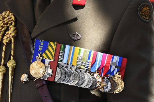 Varias medallas cuelgan del saco de un veterano, durante el desfile del Día de los Veteranos en N.Y.