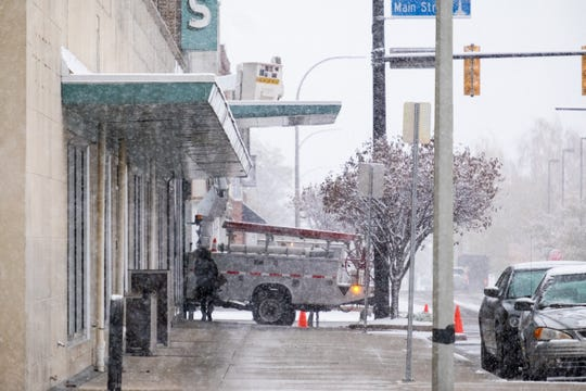 A woman takes cover from snow under the overhang outside Sperry's as she walks along the sidewalk Monday, Nov. 11, 2019, in Port Hruon. The National Weather Service has issued a winter storm warning for the area, effective until Tuesday morning.