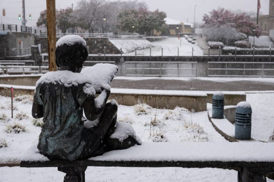 A statue of a child reads a snow-covered book Monday, Nov. 11, 2019, in downtown Port Huron.