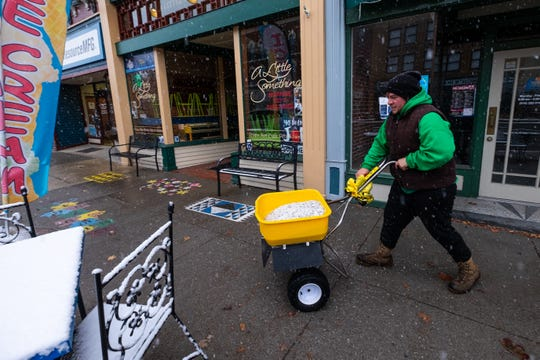 Chris Camm, with Clean Cut Maintenance LLC, spreads salt on a downtown sidewalk Monday, Nov. 11, 2019, in Port Huron. The National Weather Service has issued a winter storm warning for the area, effective until Tuesday morning.