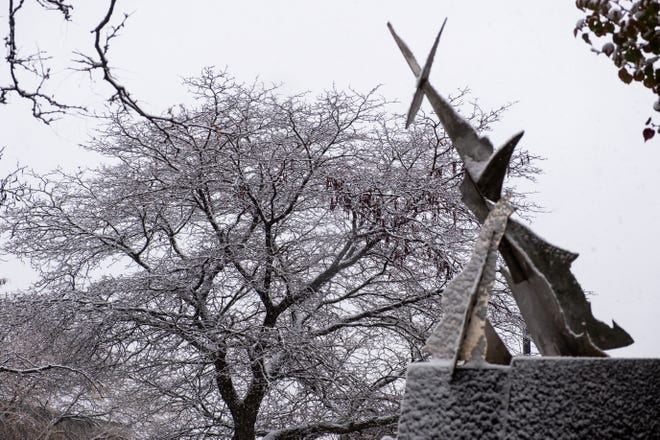 Snow covers a sculpture and mostly-bare tree Monday, Nov. 11, 2019, in Port Huron.