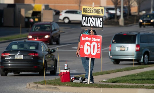 A sign is held along Carlisle Road announcing the closure of Dressbarn in West Manchester Township.