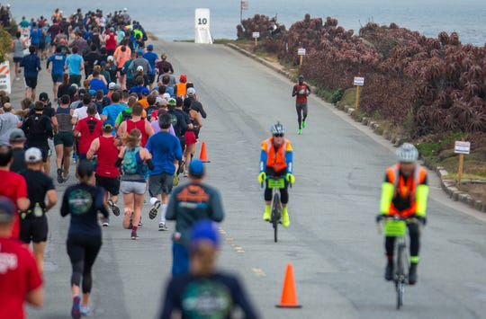 Victoy Chepnengo, runs pass the rest of the participating runners during the Monterey Bay Half Marathon in Monterey, Calif. on Sunday, Nov. 10, 2019. Chepnengo breaks the women's record by over a minute and half.