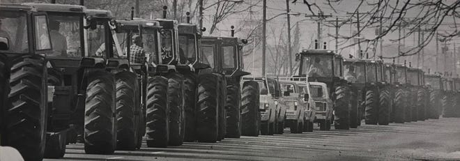 A long line of tractors and farm trucks carry frustrated farmers into San Angelo  to protest poor the 1977 Farm Bill passed by the US Congress, which they said contains an unacceptably high level of disparity for American agriculturists, who were suffering from poor market conditions at the time.