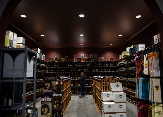 Customers shop around the wine cellar inside JJ's Wine, Spirts and Cigars on Friday, Nov. 8, 2019 in Sioux Falls.