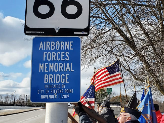 Members of American Legion Post 6 perform a rifle salute Monday, Nov. 11, 2019, during the rededication of the Clark Street Bridge as the Airborne Forces Memorial Bridge.