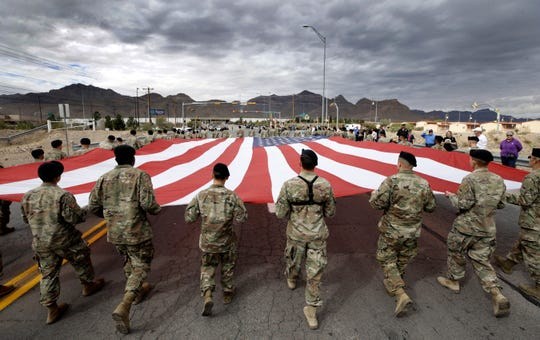 Fort Bliss soldiers march the giant 100 x 50 foot American Flag to the Old Glory Memorial site during the Northeast Veteran's Day Parade on Monday.