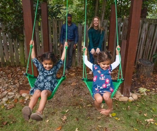 Prem and Meghan Patel push their twin daughters Zara, left, and Jai, right, on swings in their backyard.