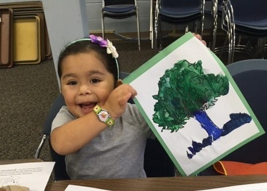 Charlize Calixto, 4, of Upper Deerfield, shares her painting during a Wee Read session at the Cumberland County Library.