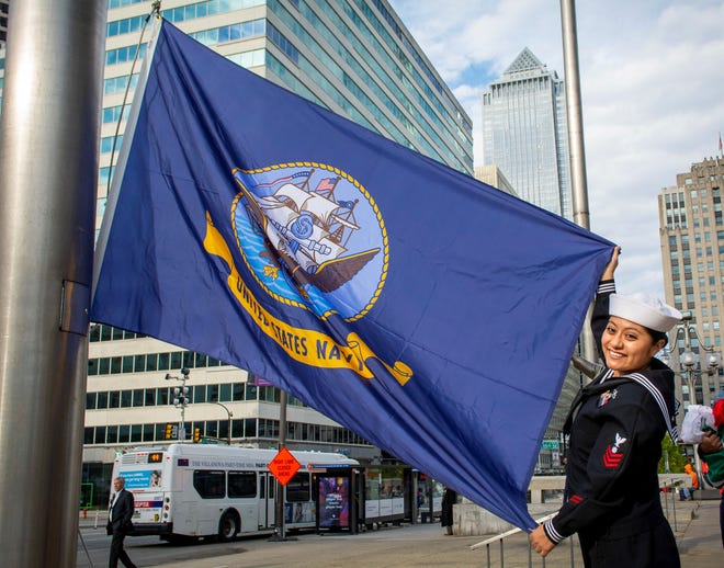 Quartermaster 1st Class Evon Perez of Bridgeton assigned to Navy Recruiting District Philadelphia, presents a Navy flag to be hoisted in front of the Philadelphia Municipal Services Building as part of the Navy's 244th birthday celebration.